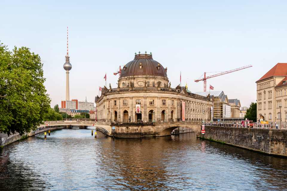 Berlin, Germany - July 27, 2019: Scenic view of Spree river and Museum Island with Monbijou Bridge, Bode and Pergamon museums and TV tower on background. View at sunset